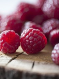 Raspberries on a Wooden Surface Photographic Print by Martina Schindler