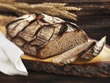 A Rustic Country Loaf on a Slice of Wood Photographic Print by Karl Newedel