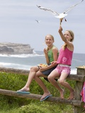 Two Girls Feeding Chips to a Seagull at the Beach Photographic Print by Louise Hammond