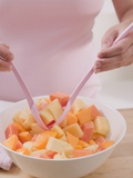 Woman Taking Fruit Salad Out of Bowl with Salad Servers Photographic Print