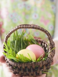 Woman Holding Basket of Coloured Easter Eggs Photographic Print