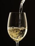 White Wine Pouring from Bottle into Glass Photographic Print by John Hay