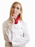 Thoughtful Blond Female Chef in Work Clothes Photographic Print by Robert Kneschke