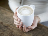 A Pair of Hands Holding a Cappuccio Cup Photographic Print