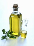 A Bottle and a Carafe of Olive Oil with an Olive Sprig Photographic Print by Alena Hrbkova