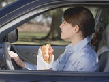 Young Woman Eating Croissant in Car Photographic Print