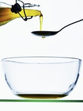Olive Oil Being Poured onto a Spoon Photographic Print by Hermann Mock