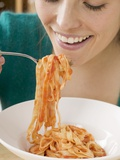 Woman Eating Ribbon Pasta with Tomato Sauce Photographic Print