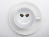 A Coffee Cup with Two Coffee Beans Making a Smiley Face Photographic Print by Jean Gillis