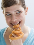 Young Woman Biting into Deep-Fried Onion Ring on Index Finger Photographic Print