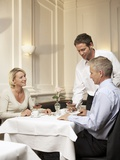 Waiter Serving a Mature Married Couple in a Restaurant Photographic Print by Manfred Gestrich