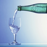 Water Being Poured from a Bottle into a Glass Photographic Print by Klaus Arras