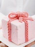 Hands Holding Cake with Marzipan Ribbon Photographic Print