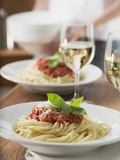 Spaghetti with Tomato Sauce and Glasses of White Wine on Table Fotografisk tryk