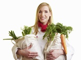 Blond Chef Holding Two Bags of Vegetables Photographic Print by Robert Kneschke