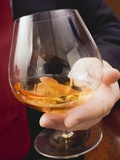 Hand Holding Glass of Cognac Photographic Print
