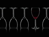 Row of Wine Glasses and a Glass of Red Wine Against a Black Background Photographic Print by Shawn Hempel