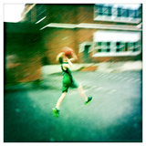 A Ten Year Old Boy Drives to the Basket on a School Playground Fotografisk tryk af Skip Brown