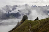 A Hiking Trail Leading to Cloud-Blanketed Mountain Peaks Photographic Print by Jonathan Irish