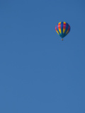 A Rmulti-Colored Hot Air Balloon Sails Through a Clear Blue Sky in Chatham County, Nc. Photographic Print by Megan Q. Daniels
