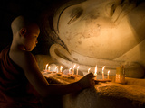 A Novice Monk Lighting Candles at a Massive Buddha Statue in Burma (Myanmar) Photographie par Kyle Hammons