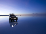 A 4X4 Rests in the Early Am Reflection in a Flooded Salt Flat In Photographic Print by Sergio Ballivian