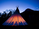 A Fire Creates a Glow from Inside a Teepee at Dusk. Photographic Print by Sergio Ballivian