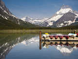 Colorful Canoes Line the Dock at Many Glacier Lodge on Swiftcurrent Lake During Sunrise Photographic Print by Brad Beck