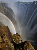 Two Rainbows Rest in Between Zimbabwe and Zambia Seen from the Zambian Side of Victoria Falls. Photographic Print by Karine Aigner