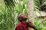 Schoolchild Embracing Tree Trunk and Looking Up, Bujumbura, Burundi Photographie par Anthony Asael