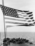 U.S. Flag Waving in Foreground over Flight Deck of an Escort Carrier, July 16, 1943 Prints