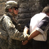 US Soldier Cuffs an Iraqi Man Suspected of Making Explosive Devices, 2007 Photographic Print