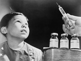 Child Looks at a Syringe with Poliomyelitis Vaccine in 1955 Photographie