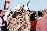 Returning US Soldier Hugs Loved One Amid Other Celebrating Families and Friends Photo