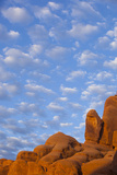 A Rock Formation Against the Blue Sky with Clouds Photographic Print by John Burcham