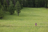 A Woman Trail Running in a Field Photographic Print by John Burcham
