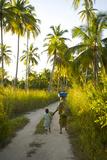 A Woman and Her Son Walking Between Fishing Villages On Matemo Island Fotografisk tryk af Jad Davenport