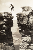 A Man Leaps From One Side to the Other Over a Break in a Rock Wall Photographic Print by  Kolb Brothers