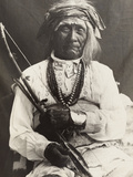 An Old War Chief, Seated On a Chair, Poses with a Bow and Arrows Photographic Print by Frederick I. Monsen