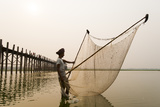 A Man Fishes Next the U Bein Bridge in Mandalay Region Photographic Print by Alex Treadway