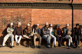 Local Men Sit on a Bench in Patan Durbar Square Photographic Print by Dmitri Alexander