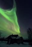 The Aurora Borealis Over a House in a Sami Village Photographic Print by Babak Tafreshi