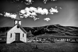 A Church and Cemetery in a Hilly Landscape with Puffy Clouds Photographic Print by Jonathan Irish