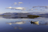 A Johnboat with An Outboard Motor and Its Reflection in Calm Blue Water Photographic Print by Jonathan Irish