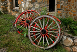 Old Wagon Wheels Lean Against a Stone Building Photographic Print by Rex A. Stucky