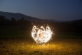 A Child Plays with Sparklers in a  Field in Lost Cove, Tennessee Photographic Print by Stephen Alvarez