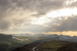 Sunlight Streaming Through Heavy Storm Clouds Over Mountains Photographic Print by Richard Olsenius