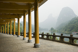 The Li River Runs Past a Covered Walkway by the Karst Formations Photographic Print by Jonathan Kingston