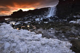 A Waterfall Cascades Into a Frozen River at Sunset Photographic Print by Raul Touzon