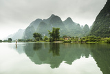A Barefoot Man Walks Across the Li River Near Yangshuo, China Photographic Print by Jonathan Kingston